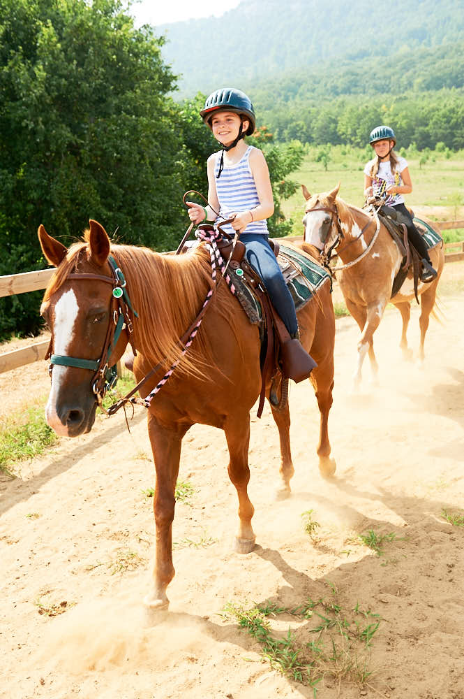 Ahrianna Keefe and Phoebe Eddleman riding horses at Camp Hanes.